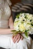 Vit bukett i händer av bruden Arkivbilder