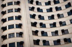 Vit byggnad med svarta Windows Arkivfoto