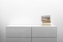 Vit byrå med bunten av böcker i ljus minimalisminre Fotografering för Bildbyråer