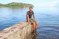 Vit Caucasian manlig handelsresande i sportswearen som sitter på en stenpir på den längsta sjön i världen royaltyfri bild
