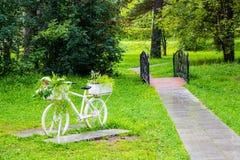 Vit cykel för tappning med korgar av blommor bland trädgården Arkivbild