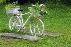Vit cykel för tappning med korgar av blommor bland trädgården Royaltyfri Foto