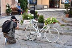 Vit cykel med blommor i Tropea royaltyfri foto