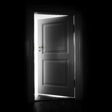 Vit dörr för öppning i ett mörkt rum Royaltyfri Foto