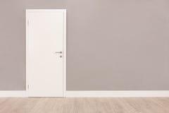 Vit dörr i ett tomt rum arkivfoto