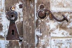 Vit dörr med nyckelhålet och handtaget arkivfoto