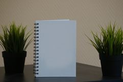 Vit dagbok med gr?na v?xter arkivfoto