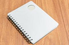 Vit dagbok på den wood tabellen Royaltyfri Bild