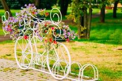 Vit dekorativ cykelparkering i trädgård Royaltyfri Foto