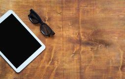Vit digital minnestavla med den svarta skärmen och svarta exponeringsglas på den wood tabellen kopiera avstånd Arkivbilder