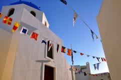Vit domkyrka för ortodox kyrka med den blåa kupolen och girlanden av flaggor av olika länder på den blåa himlen Royaltyfri Fotografi