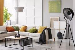 Vit elegant hörnsoffa med orange gröna och gula kuddar i stilfull vardagsrum som är inre med den modern kaffetabellen och indust royaltyfria bilder