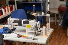 Vit elektrisk industriell symaskin i ett seminarium för att sy och att arbeta arkivbild