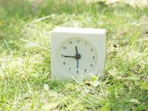 Vit enkel klocka på gräsmattagården, 11:45 elva fyrtiofem Fotografering för Bildbyråer