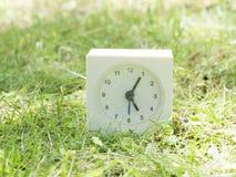 Vit enkel klocka på gräsmattagården, 5:05 fem fem Fotografering för Bildbyråer