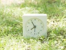 Vit enkel klocka på gräsmattagården, 7:55 sju femtiofem Arkivfoto