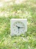 Vit enkel klocka på gräsmattagården, 10:15 tio femton Arkivbilder