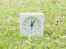 Vit enkel klocka på gräsmattagården, 12:05 tolv fem Royaltyfri Fotografi