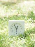 Vit enkel klocka på gräsmattagården, 12:55 tolv femtiofem Arkivbild