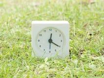 Vit enkel klocka på gräsmattagården, 12:20 tolv tjugo Arkivfoto