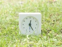 Vit enkel klocka på gräsmattagården, 12:25 tolv tjugofem Royaltyfria Bilder