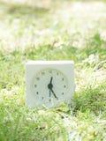 Vit enkel klocka på gräsmattagården, 12:25 tolv tjugofem Fotografering för Bildbyråer