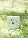 Vit enkel klocka på gräsmattagården, 3:55 tre femtiofem Arkivbilder