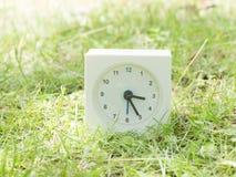 Vit enkel klocka på gräsmattagården, 3:25 tre tjugofem Royaltyfria Bilder