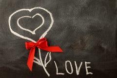 Vit FÖRÄLSKELSE som hälsar meddelandet med hjärtasymbol på svart tavla Arkivfoto