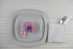 Vit för inbrott för påskschemaställe och dekorerat med rosa spräckliga ägg och en muffin med den ätliga blomman Fotografering för Bildbyråer