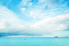 Vit fördunklar i den blåa himlen över havet arkivfoto