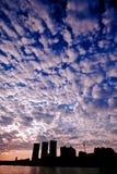 Vit fördunklar på en blå himmel och en stad Royaltyfri Fotografi