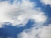 Vit fördunklar spegeln för blått vatten Arkivbild
