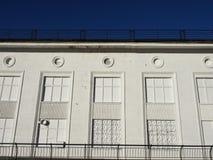 Vit fasad av huset med ett smidesjärngaller på en serie av imaginära fönster Royaltyfri Bild