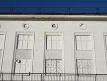 Vit fasad av huset med ett smidesjärngaller på en serie av imaginära fönster Arkivfoton
