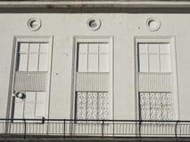 Vit fasad av huset med ett smidesjärngaller på en serie av imaginära fönster Arkivfoto