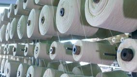 Vit fiber som köar på spolar som förläggas på kuggar på en fabrik lager videofilmer