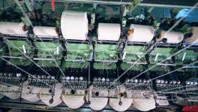 Vit fiber som rullar ihop på stora rullar på en textilväxt lager videofilmer