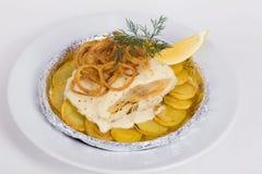 Vit fisk med potatisar, stekte lökar, dill fotografering för bildbyråer