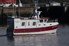 Vit fiskebåt för röd anf som är kommande i hamnen Arkivfoton