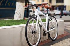 Vit fixa-kugghjul cykel på gatan royaltyfri foto