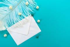 Vit fjäder för vitt kuvert och blå stearinljus som isoleras på blå bakgrund Begrepp f?r h?lsningkort arkivbilder