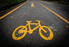 Vit fläck av cykel- och vitpilen som pekar en väg på asfaltbanan Royaltyfri Foto