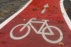 Vit fläck av cykel- och vitpilen som pekar en väg på asfaltbanan Arkivfoton