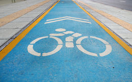 Vit fläck av cykel- och vitpilen som pekar en väg på asfaltbanan Arkivbilder