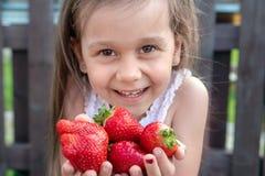 Vit flicka med l?ngt svart h?r som rymmer jordgubbar royaltyfria bilder