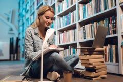 Vit flicka nära bokhyllan i arkiv Studenten tar anmärkningar royaltyfria foton