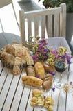 Vit franskbröd på träbräde med exponeringsglas av vin Arkivfoto