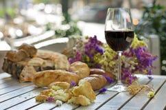 Vit franskbröd på träbräde med exponeringsglas av vin Royaltyfri Foto