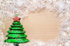 Vit frostiga filialer som är dolda med snö, leksakjulgranen för grönt exponeringsglas och kopieringsutrymme på naturlig träbakgru Arkivbild